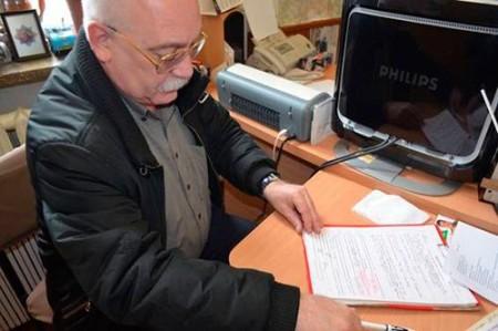 Мужчина за столом работает с бумагами